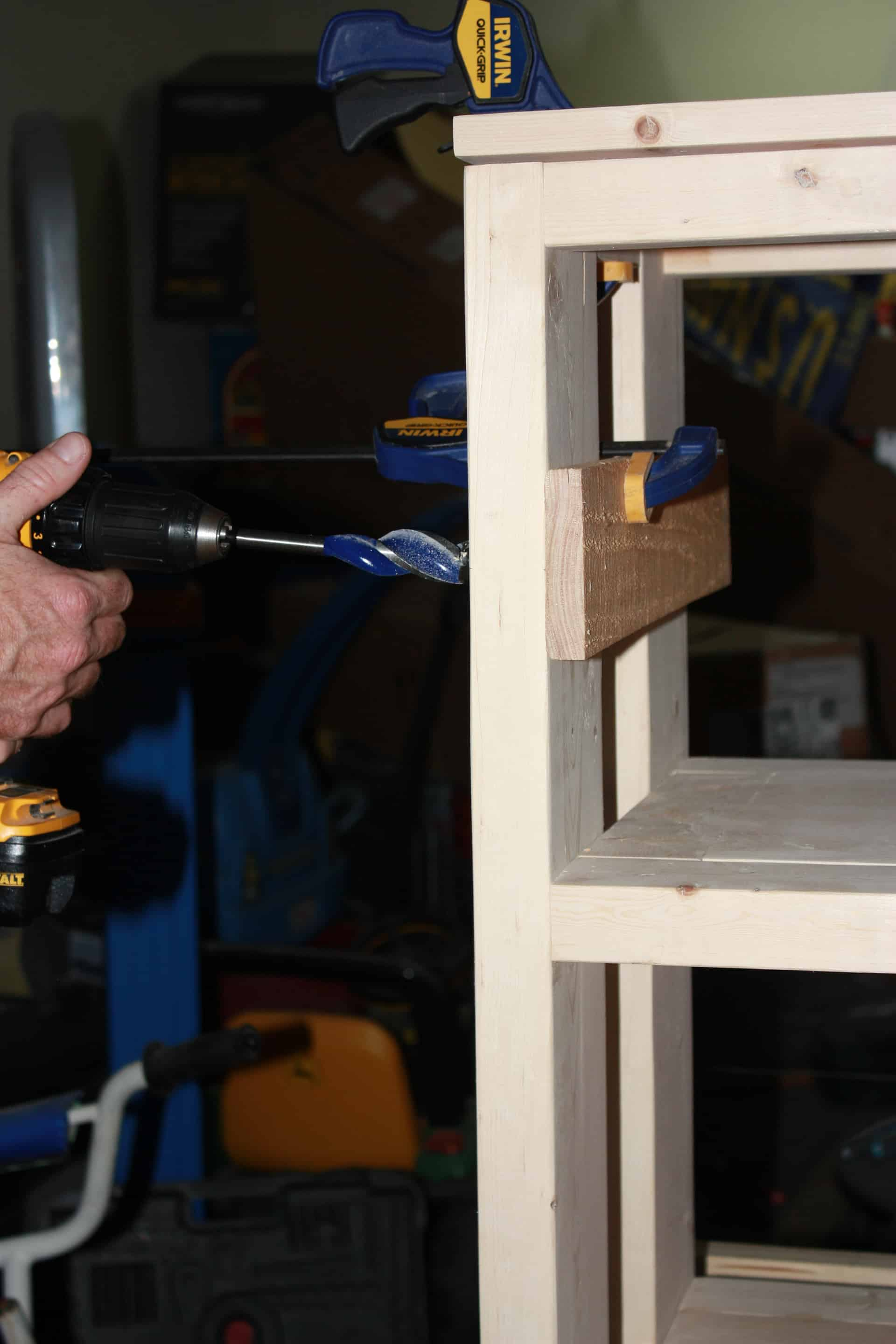 Drilling the holes for the pipe on the wood and steel console table