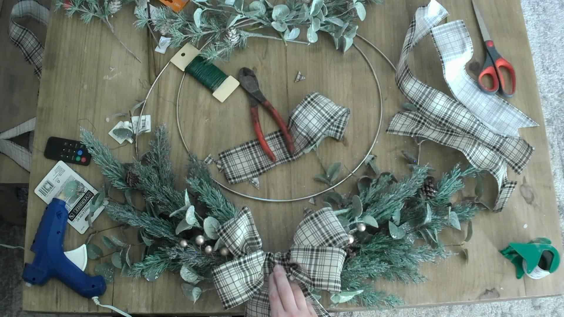 Attaching the bow to the DIY Christmas wreath