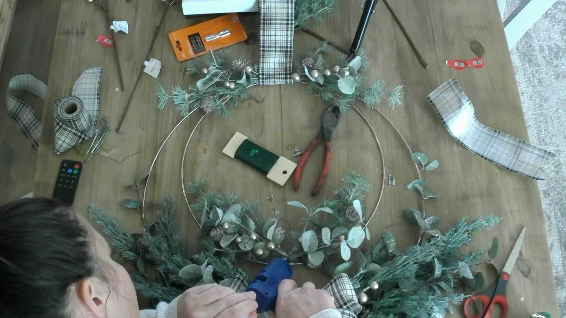 Hot glueing the stems into place on the DIY Christmas Wreath