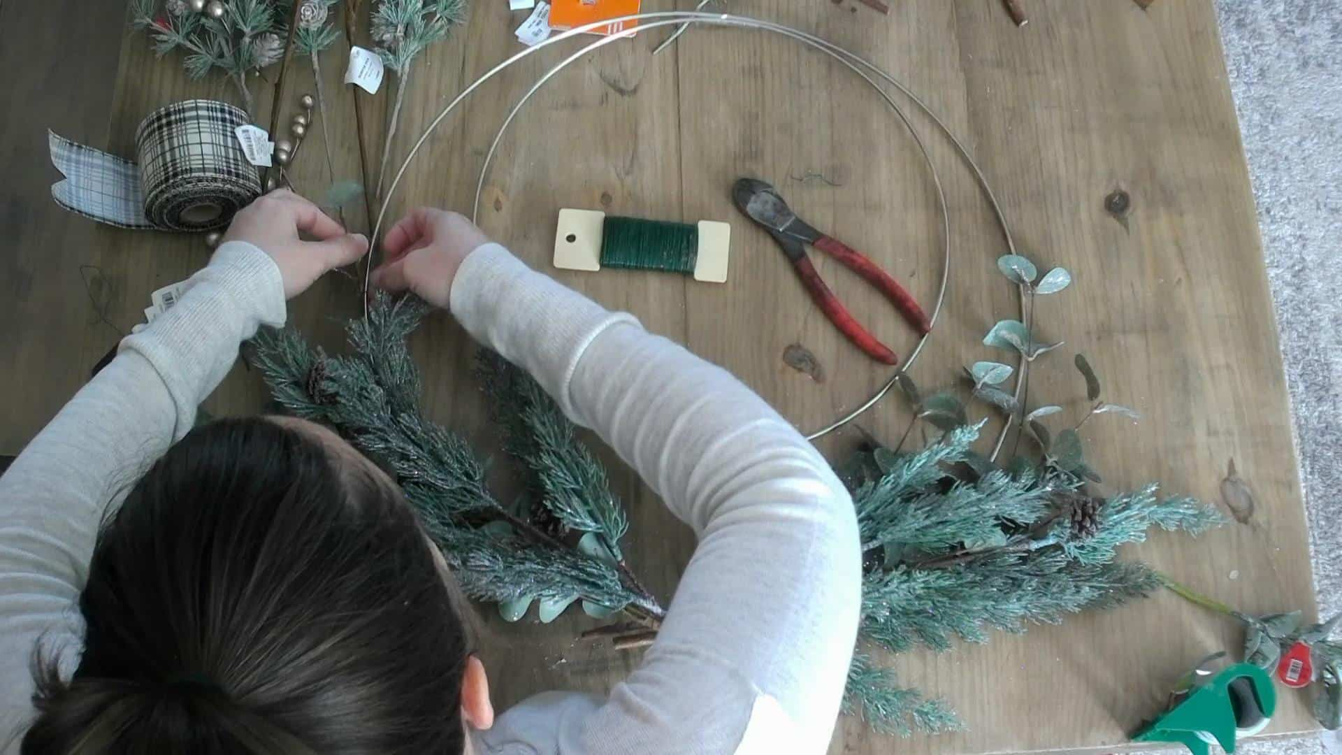 Adding the greenery to the DIY christmas / winter wreath